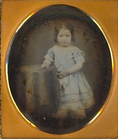 Girl in blue dress holding china head doll by Mirror Image Gallery, via Flickr