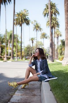 Aimee Song of Song of Style wearing a blazer, button-down shirt, and strappy yellow heels