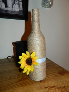 Old wine bottle covered with twine and accented with ribbon and sunflower.