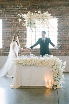 Chic Warehouse Wedding - the perfect neutral wedding colors at an Arizona warehouse wedding. Lush cream and white floral arrangements with textured designs. Wedding flowers of orchids, roses, anthurium, and ranunculus were seen in the large bridal bouquet, altar pillar flowers for the wedding ceremony, full sweetheart table flower garland at the industrial wedding reception, and hanging wedding arrangement of flowers. Photos by Lea Bremicker.  #weddingflowers #elegantwedding Bridal Table, Table Wedding, Wedding Decor, Wedding Reception, White Floral Arrangements, Wedding Arrangements, Neutral Wedding Flowers, Fall Wedding Colors, Elegant Bride