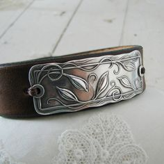 Wonderful leather cuff with metal clay accent.