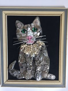 This is a handmade jewelry art cat!! One of a kind! All the jewelry ranges from contemporary to vintage and is from necklaces, bracelets, brooches, and earrings. This cat features silver toned jewelry, with white and off white beads and pearls. The eyes are green rhinestones with