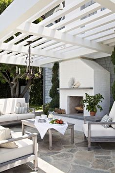modern white pergola with stone flooring, bleached wood furnishings and painted brick house