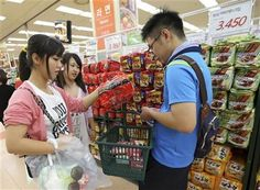 "In this Aug. 18. 2014 photo, customers pick up a package of ""ramyeon"" instant noodles in a basket at a shopping center in Seoul, South Korea. (AP Photo/Ahn Young-joon) ▼21Aug2014AP