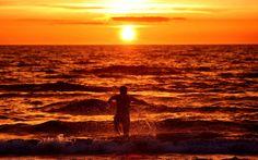 Güneş Hiddensee, Almanya, Baltık Denizi adasında Vitte yakın ayarı yaparken bir adam suya çalışır