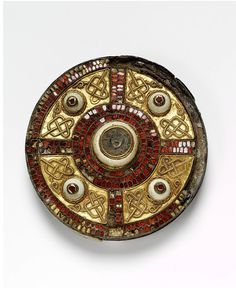 The Milton Disc Brooch. Kent, England (probably, made) 600-700. Silver, bronze, gold, garnet, shell. The Milton Jewel is one of the finest examples of Anglo-Saxon brooches of the period, with a sophisiticated design carried out in a combination of materials.The use of cloisons inlaid with garnet, filigree knot work decoration on gold sheet and shell bossess are typical of this type. The brooch was found in 1832 in a cemetery at Milton, west of Dorchester-on-Thames.