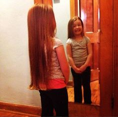 That smile! Olesia grins at herself in the mirror, excited to chop off her hair to help others