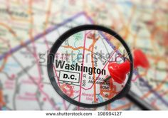 Closeup of a map of Washington DC with red pin and magnifying glass