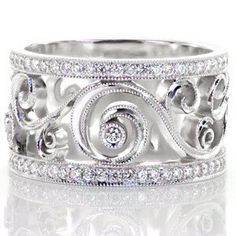 Lulu Bea - Lulu is a mesmerizing design full of movement and graceful curves. The pattern spirals and twists like ribbons ending in a full bezel set diamond. The delicate design is framed in a milgrain edge, as well as two micro pavé diamond bands. This exquisite design is truly one of a kind.