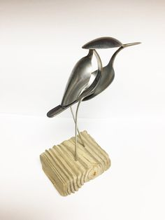 Bird made from upcycled utensils and scrap metal perched on reclaimed wood.  Height: 7.5  Length: 6.25  Width: 2.5