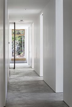 Beautiful minimalist hallway with pivot door and large window framing the landscape beyond.    Tact Architecture have designed the Carling Residence in the Muskoka region of Ontario, Canada.