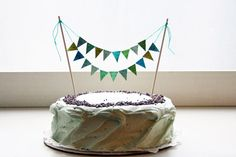 DIY Mini pennant garland for a cake  (these instructions glitter the pennants but you could write letters on them to spell out words instead)