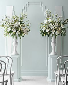 Crisp white ceremony marker arrangements. Not the color so much as the look... Pedestals on either side.