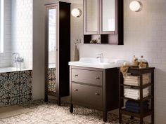 Łazienka z białymi kafelkami, białą szafką z umywalką GODMORGON i pomarańczowym dywanikiem.