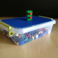 Road trip worthy Lego Box - plastic bin that has handles with Lego board attached (just use scissors to cut board to size)