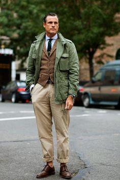 Light blue shirt, dark blue ties, brown cardigan, green field jacket, khakis, brogues.