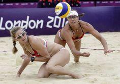 The United States's Misty May Treanor, right, dives over her teammate Kerri Walsh Jennings during a women's semi-final beach volleyball match against China at the 2012 Summer Olympics, Tuesday, Aug. 7