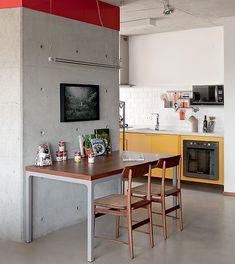Junto à coluna de concreto fica a mesa da copa, móvel do Atelier Fernando Jaeger. Ela também serve de apoio para livros de receita, já que o ambiente é conectado à cozinha. Projeto do escritório dt.estudio