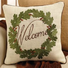 White burlap 'Welcome' pillow features embroidered acorn wreath design and contrasting piped edging.