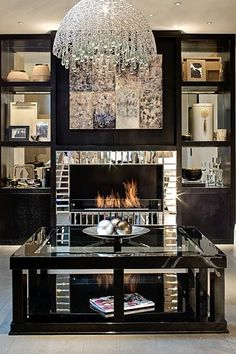 A black-lacquered entertainment center and coffee table are warmed up by cream-colored accents (and a fireplace framed in mirrored tiles doesn't hurt either).   - HarpersBAZAAR.com
