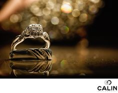 Photography by Calin - wedding rings one king west: For this wedding ring photo taken at One King West, I placed the rings on a reflective surface, lit the image from above to get this soft light. For the bokeh behind, I positioned bride's shoes so that they created that superb effect. I used a 100mm Canon macro lens and positioned the front of the lens 1 inch from the rings. . Location: 1 King Street West Toronto, ON M5H 1A1 .