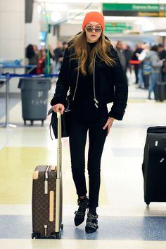 Gigi Hadid aposta em look all black + toca laranja e óculos para completar seu look de aeroporto.