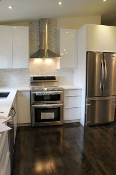 Ikea Abstrakt white high gloss kitchen cabinets with white quartz counters and calacatta marble bullets for the backsplash