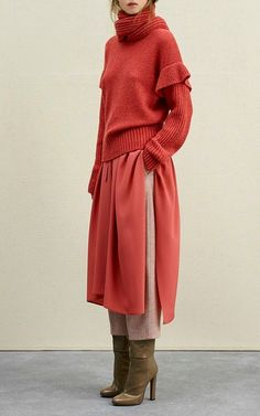 A bright orange red, large oversized jumper with a fold down turtleneck, over a bright orange red, a slightly lighter hue, side split a-line knee length full skirt, underneath the skirt a pair of beige trousers with a pegged leg and dark olive coloured suede high heeled boots by Angona Pre Fall 2017
