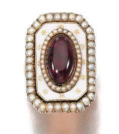 ENAMEL AND SEED PEARL MOURNING RING, CIRCA 1785.    The mount decorated with white enamel, seed and half pearls, later set with a cabochon foiled back garnet, inscribed to reverse, 'J A died 10th August 1788, aged 17'