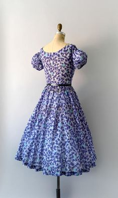 1950s vintage dress, purple floral light-weight cotton, scoop neck, dropped shoulders with capped puffed sleeves, fitted waist, very full skirt, hidden side metal zip closure. - - - M E A S U R E M E N T S - - - Fit/Size: Small Bust: 34 Waist: 25 Hips: free Length: 43 Maker/Brand: