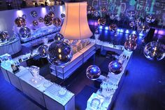 Silver and copper spheres hung from a square truss structure over the trading floor. An eight-foot lampshade from Eurolites illuminated...