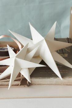 Voor deze 3D-sterren heb je nodig: papier, schaar, lijm en een potlood! Maak er een stilleven van met oude kerstballen en doosjes. En kerstproof is je huis!