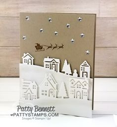 Hearts Come Home Christmas card featuring Whisper White die cut village houses and Santa and his reindeer in the sky with Silver Enamel Metallic stars.