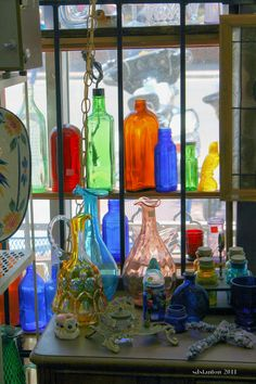 I was in an antique store today and I couldn't resist taking this shot of the lovely colored glass bottles in the window.