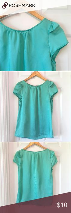 Aqua Blouse Cute aqua blue top. Has cap style sleeves with a ruffle design. There is a snag in the fabric on the back, shown in the last picture. Worn once! Tops