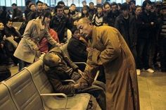 A monk prays for an elderly man who died suddenly while waiting for the train in Shanxi Taiyuan in China.