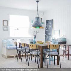 Vintage-Stühle aus den 50ern und 60ern lassen sich wunderbar zu schlichten Holzmöbeln kombinieren. Die Nummerierungen auf den Rückenlehnen, eine Deckenlampe aus Metall sowie blau-weiße Dekoartikel erzeugen in Kombination mit dem hellen Holzfußboden und den weißen Dielenwänden eine nostalgische, gemütliche Atmosphäre.