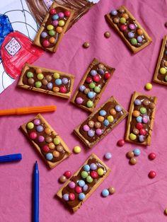 De la pâte sablée du chocolat au lait et des smarties et c'est parti ! Découper des rectangles de pâte sablé, à peu près la taille d'un moule à financiers. Piquer les fonds avec une fourchette et placer au frais 1 à 2 heures. Préchauffer le four à 180°. Faire cuire les fonds de biscuits 5 à 8 min (quand c'est doré c'est bon). Faire fondre le chocolat au lait au micro-ondes, et le couler dans les fonds de pâte sablée. Ajouter des smarties, et laisser prendre.
