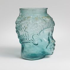 Glass cup in the form of the head of an African.   MET.  Period:Early Imperial,Flavian  Date: 2nd half of 1st century A.D.Culture:Roman  Medium:Glass; blown in a three-part mold  Dimensions:H. 10.5cm  Classification:Glass  Credit Line:Gift of Henry G. Marquand, 1881  Accession Number:81.10.226