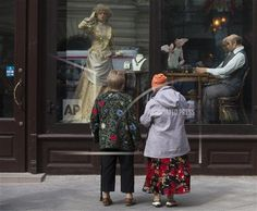 Two elderly women look at a shop show case near Red Square in Moscow, Russia, Saturday, Sept. 6, 2014. Celebrations marking the Day of Moscow were held in Red Square on Saturday. (AP Photo/Alexander Zemlianichenko)