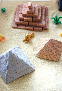 """On continue notre exploration de l'Egypte ancienne, cette fois-ci avec un bac sensoriel dédié au site de Gizeh : trois pyramides et un grand sphinx. On a utilisé plusieurs matériaux pour nos monuments. Je voulais vraiment utiliserdu vrai sable, mais je n'ai rien trouvé dans mon coin ou alors vraiment très cher pour une petite quantité. A la place, j'ai donc pris de la semoule fine. Khéops a été construite avec des """"briques"""" de sucre roux que j'avais mis de côté après l'avoir déjà utilisé…"""