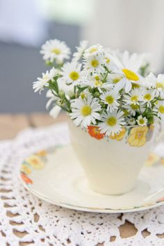 Daisies in a teacup. fabulous. I could do this with my assortment of tea cups I've collected thru the years. something different to do with them. YES!!