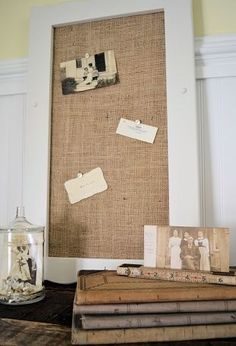 Burlap covered cork board. Do it with black cloth and silver/ white border with floral pattern. Use existing boards and glue on the fabric. Cardboard the back for more support. Hang over the desk.