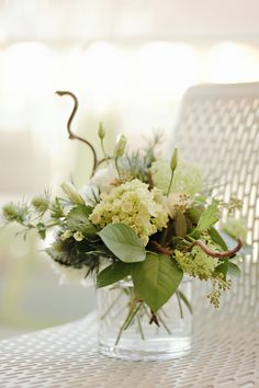 table arrangement in shades of green  with hydrangea, hazel, lisianthus, thistle and guelder rose in a cylinder vase.