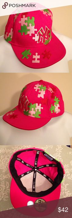 NY Yankees Pink Puzzle Piece MLB cap 7 1/2 New Era EUC bright pink with multi-colored embroidered puzzle pieces. Under bill is red with holographic MLB sticker and New Era 59Fifty size 7 1/2 label. MLB embroidered logo on back; New Era flag logo on left. Interior cotton lined, front interior is cooling mesh. New Era Accessories Hats