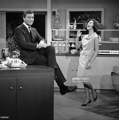 American actors Dick Van Dyke and Mary Tyler Moore share a humorous moment on an episode of 'The Dick Van Dyke Show,' Culver City, California, 1963. Van Dyke, dressed in a suit and tie, crossed his legs as he sits on a kitchen island countertop, while Moore, in a skirt and heels, stands nearby and tilts her head back, laughing.