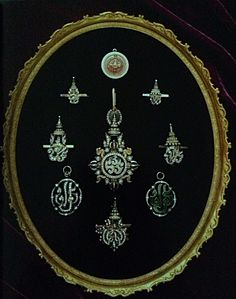 Various pins and lockets of  royal initials with precious gems and diamonds.