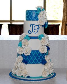 Royal Blue and Aqua wedding cake over flowing with garden roses!  Created by cakeglam.com