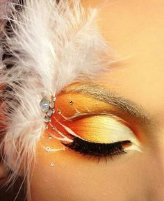 Feathers and crystals adorn artistic gold to orange gradient eye shadow.