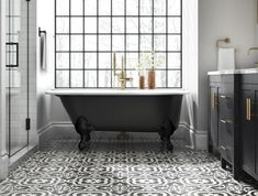 Clawfoot tub resting on a patterned floor created using black and white tile.